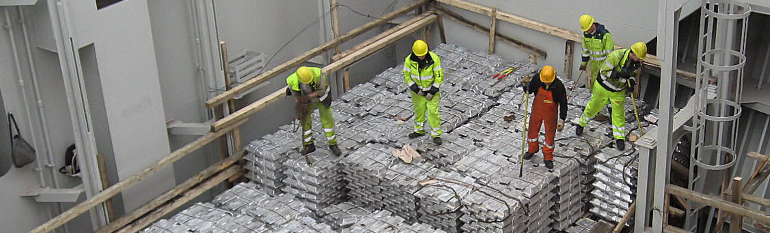 Workers on top of aluminium stacks in warehouse